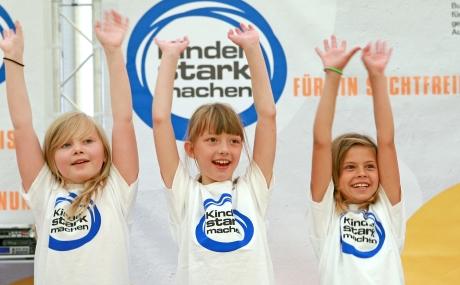 """Drei Mädchen strecken lächeln die Arme vor einer """"Kinder stark machen""""-Fotowand in die Luft"""